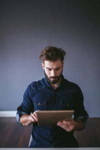 Hipster guy using digital tablet in home office